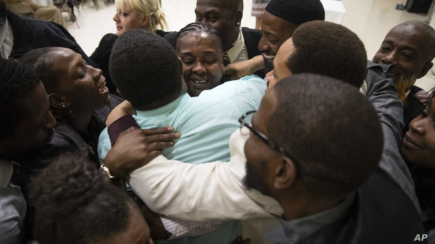 FILE - Paulette Carrington (C), a former juvenile lifer and participant in Uplift Solutions' job training program for former inmates, is embraced by her classmates during a graduation ceremony in Philadelphia, Oct. 16, 2017.