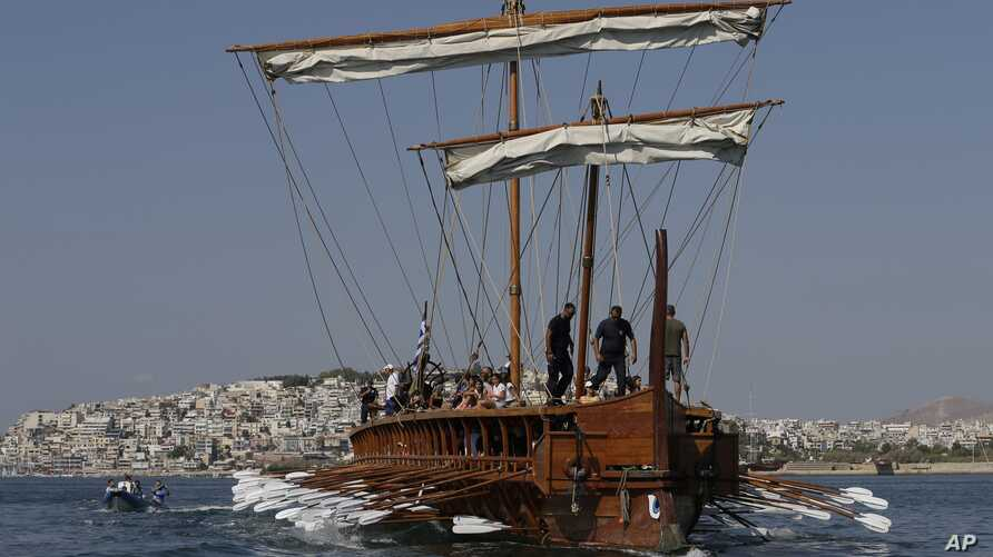 FILE - Visitors row the Olympias, a replica of an ancient galley, at Saronic gulf in southern Athens.