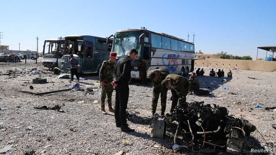Iraqi security forces inspect the site of a blast where a suicide bomber detonated his explosives-laden ambulance in Iraq's holy city of Samarra, north of Baghdad, Nov. 6, 2016.