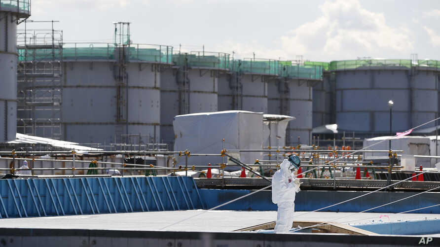 FILE - a worker, wearing protective suits and masks, takes notes in front of storage tanks for radioactive water at the tsunami-crippled Fukushima Dai-ichi nuclear power plant, operated by Tokyo Electric Power Co. (TEPCO), in Okuma, Fukushima Prefect