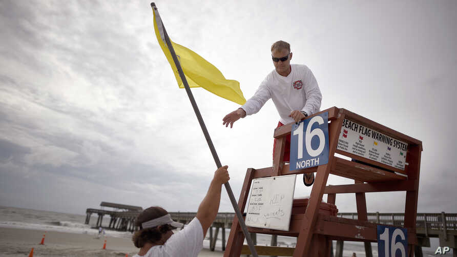 Tybee Island Ocean Rescue Senior Lifeguard Todd Horne, right, and Mark Eichenlaub, left, hang a yellow flag that warns swimmer of strong rip currents from Hurricane Arthur along the beach, on Tybee Island, Ga., July 3, 2014.