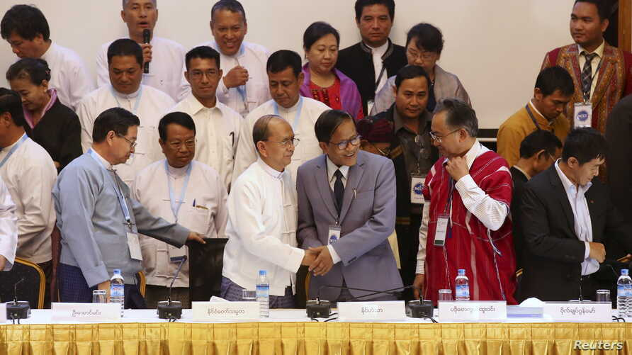 Myanmar President Thein Sein (front 3rd L) and Naing Han Tha (front 3rd R), a leader of the Nationwide Ceasefire Coordinating Team (NCCT), shake hands after signing a nationwide ceasefire draft agreement at the Myanmar Peace Center in Yangon, March 3