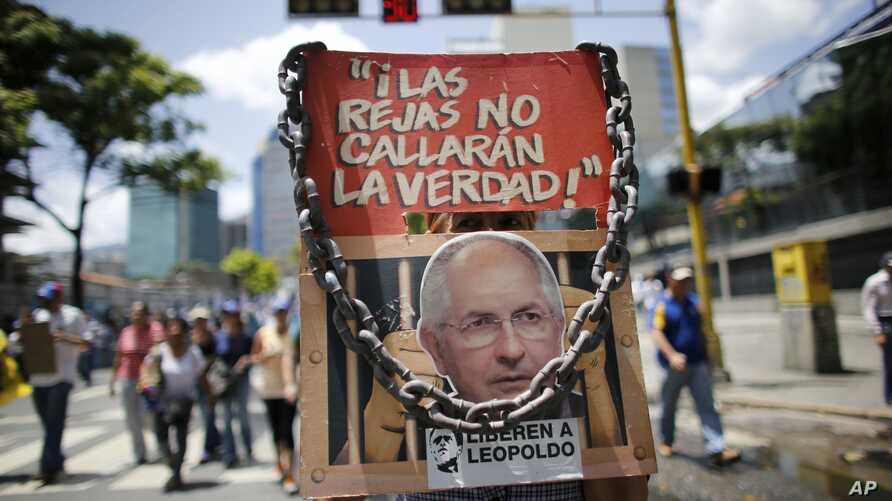 """Anti-government demonstrators holds a poster that reads in Spanish """"The jails won't shut the truth"""" and the image of opposition leader arrested Antonio Ledezma during a protest against Venezuela's President Nicolas Maduro in Caracas, Venezuela, Aug."""