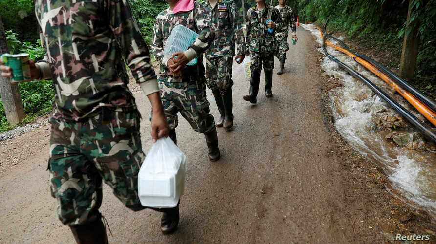 Rescue workers carry aid provisions near the Tham Luang cave complex in the northern province of Chiang Rai, Thailand, July 4, 2018.
