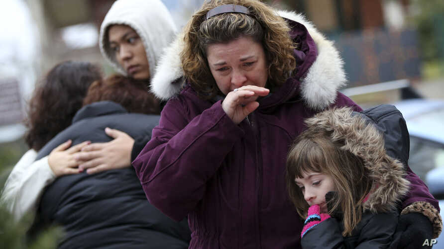 Mourners grieve at one of the makeshift memorials for victims of the Sandy Hook Elementary School shooting, December 16, 2012, in Newtown, Conn.
