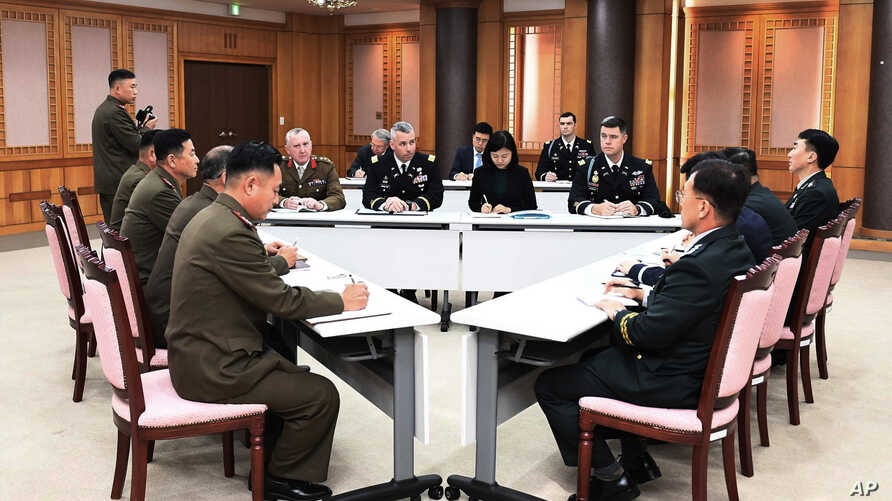 In this Oct. 16, 2018, photo provided by S. Korea Defense Ministry, the U.S.-led UNC, center, S. Korean and N. Korean, left, military officers attend a meeting at the southern side of Panmunjom in the DMZ, South Korea.
