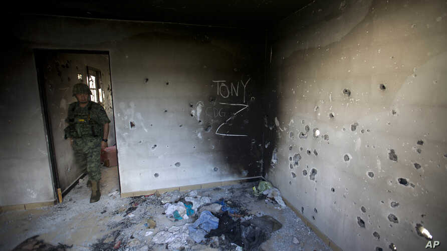 FILE - In this Sept. 6, 2014 file photo, a soldier enters a bullet-riddled home, tagged with the initials CDG for the Gulf Cartel, and Z for Zetas, in Ciudad Victoria, in Mexico's state of Tamaulipas.