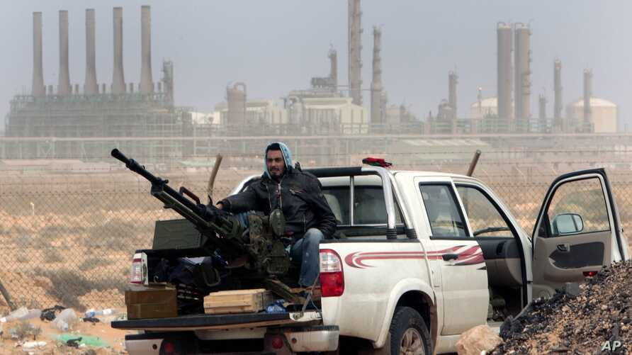 FILE - An anti-government rebel sits with an anti-aircraft weapon in front an oil refinery in Ras Lanouf, eastern Libya, March 5, 2011. The United States, France, Germany, Italy, Spain and Britain have called upon forces loyal to a Libyan general to ...