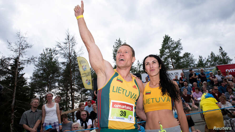 Vytautas Kirkliauskas of Lithuania and his wife, Neringa Kirkliauskiene, celebrate after winning this year's World Wife-Carrying Championship in Sonkajarvi, Finland, July 7, 2018.