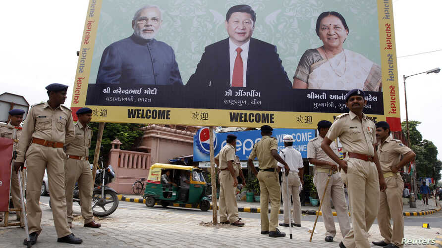 Police stand guard in front of a bill board with images of (L-R) India's Prime Minister Narendra Modi, China's President Xi Jinping and Anandiben Patel, Chief Minister of the western Indian state of Gujarat, ahead of Xi's arrival, in Ahmedabad, Sept.