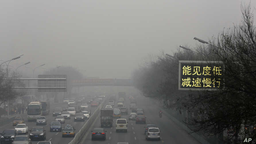 """Vehicles drive along a road with a traffic sign reading """"Visibility low, slowdown the speed"""" on a heavily polluted day in Beijing, Monday, Nov. 30, 2015."""