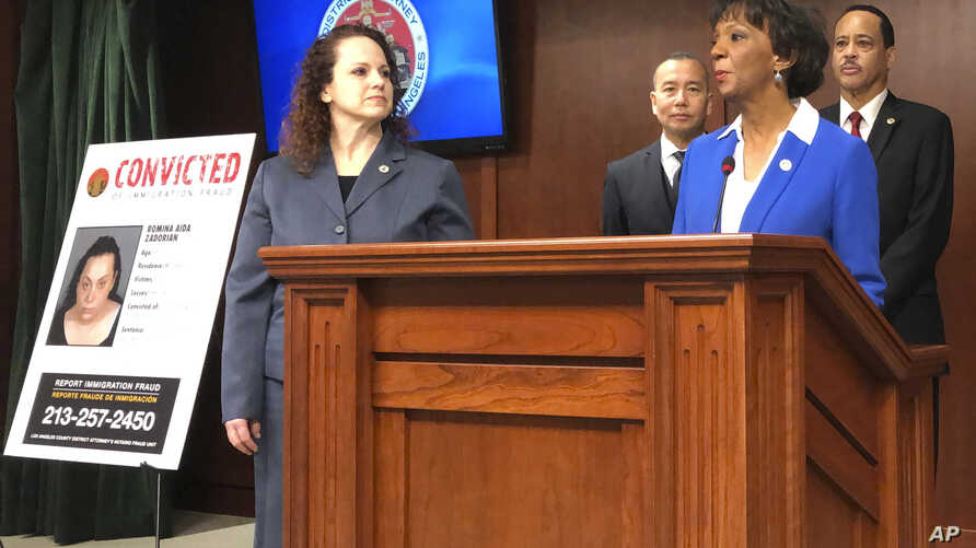 Prosecutor Ryann Jorban, left, who is on the immigrant fraud unit, looks on as District Attorney Jackie Lacey announces prosecutions during a news conference in Los Angeles, Feb. 12, 2019.