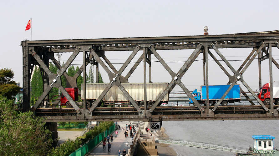 Trucks wait for border inspection at the Chinese end of the Friendship Bridge that connects Sinuiju, North Korea, with Dandong, Liaoning province, China, over the Yalu River, May 24, 2018.