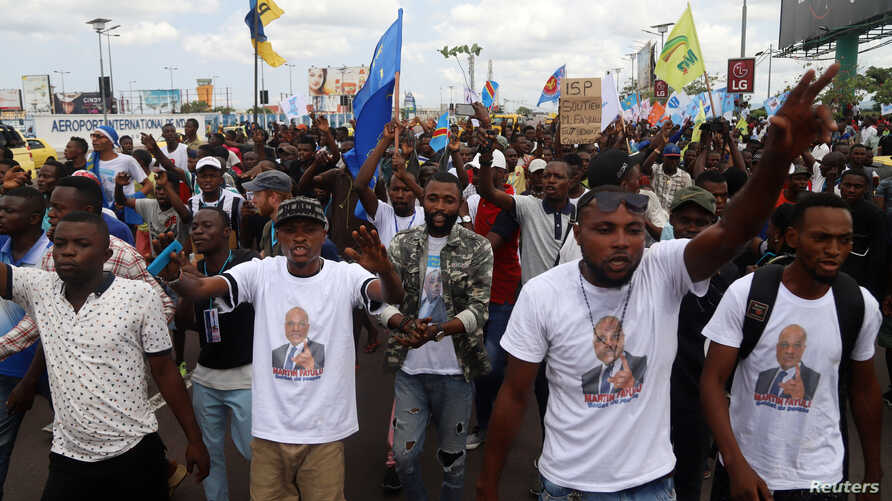 Supporters of Congolese opposition presidential candidate Martin Fayulu chant slogans as they welcome him at N'djili International Airport in Kinshasa, Democratic Republic of Congo, Nov. 21, 2018.