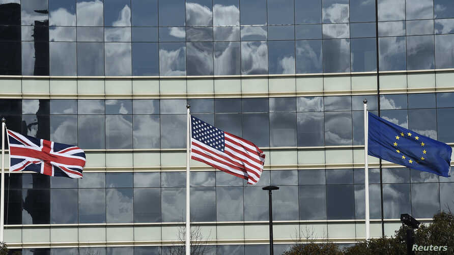 FILE - A British Union flag (L) and U.S. flag are seen flying in front of an office building in London, Britain, March 30, 2016.