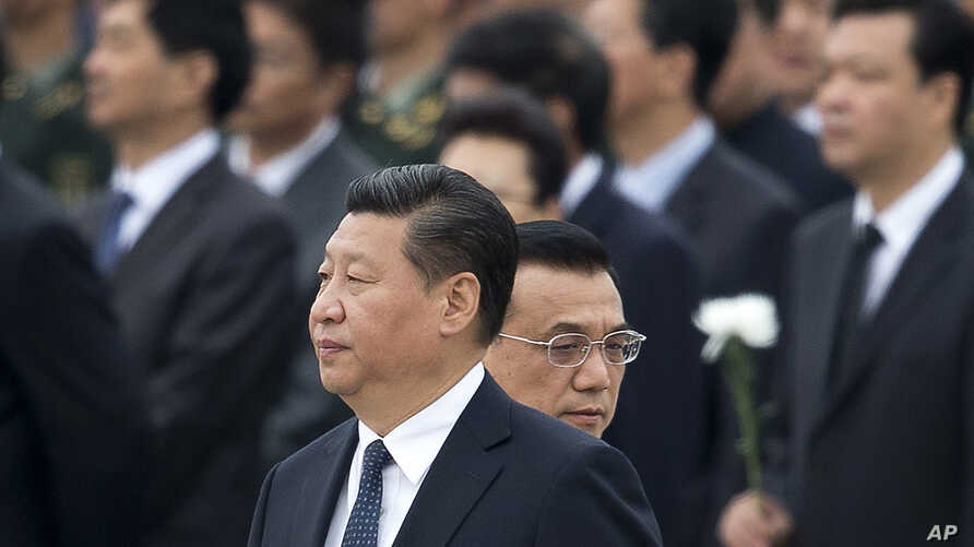 FILE - Chinese Premier Li Keqiang, right, walks past Chinese President Xi Jinping as they arrive to the Monument to the People's Heroes during a ceremony marking Martyr's Day at Tiananmen Square in Beijing, China, Sept. 30, 2014.