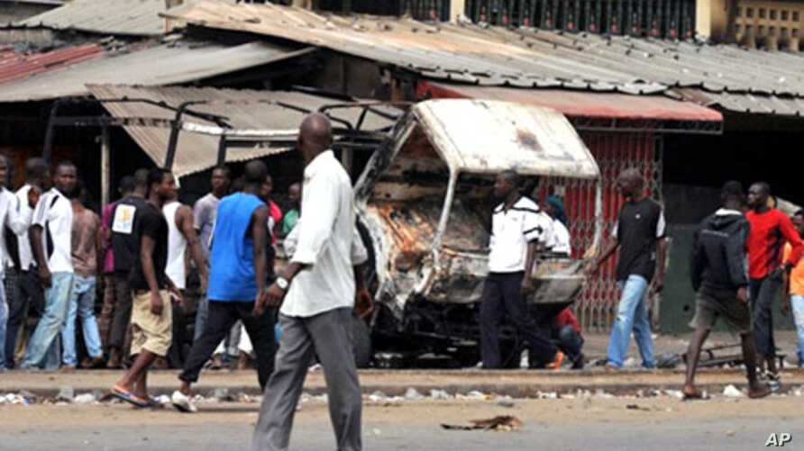 Residents look at a vehicle of FDS - troops loyal to incumbent president Laurent Gbagbo - burned in the Abobo district of Abidjan, 12 Jan 2011