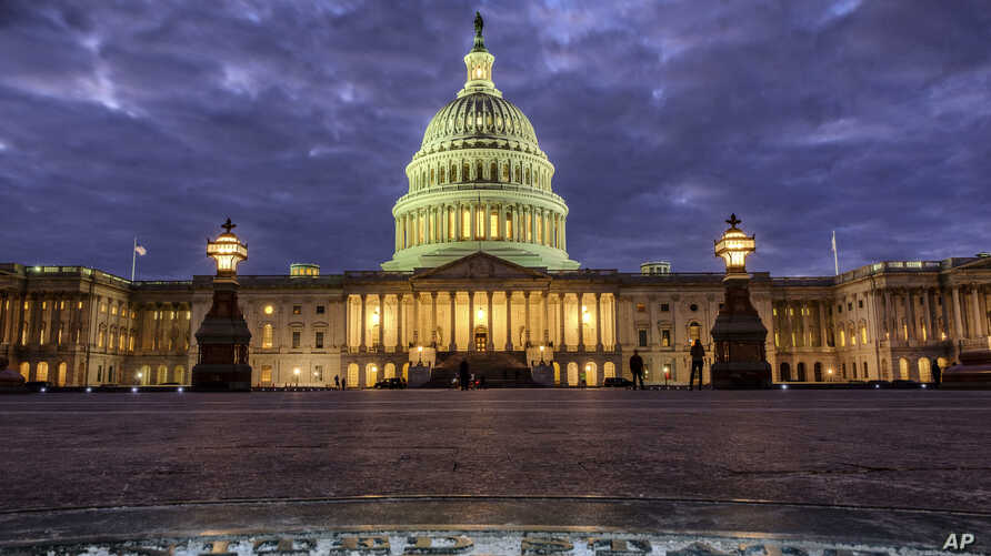 FILE - In this Jan. 21, 2018, file photo, lights shine inside the U.S. Capitol Building as night falls in Washington.