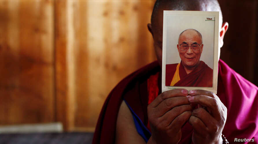 FILE - A monk holds a picture of Tibetan spiritual leader Dalai Lama inside of his room at Labrang Monastery in Xiahe county, Gansu Province Feb. 21, 2012.