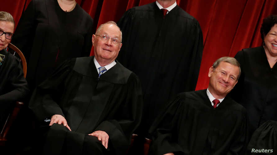 FILE - U.S. Supreme Court Justice Anthony Kennedy (L) reacts while chatting with Chief Justice John Roberts (R) during a new U.S. Supreme Court family photo.
