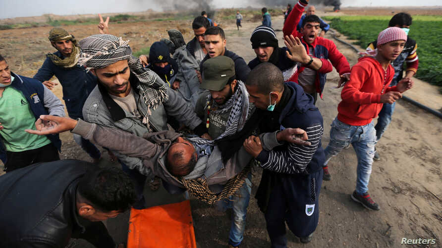 A wounded Palestinian demonstrator is evacuated during clashes with Israeli troops at a protest against U.S. President Donald Trump's decision to recognize Jerusalem as the capital of Israel, near the border with Israel in the southern Gaza Strip, De