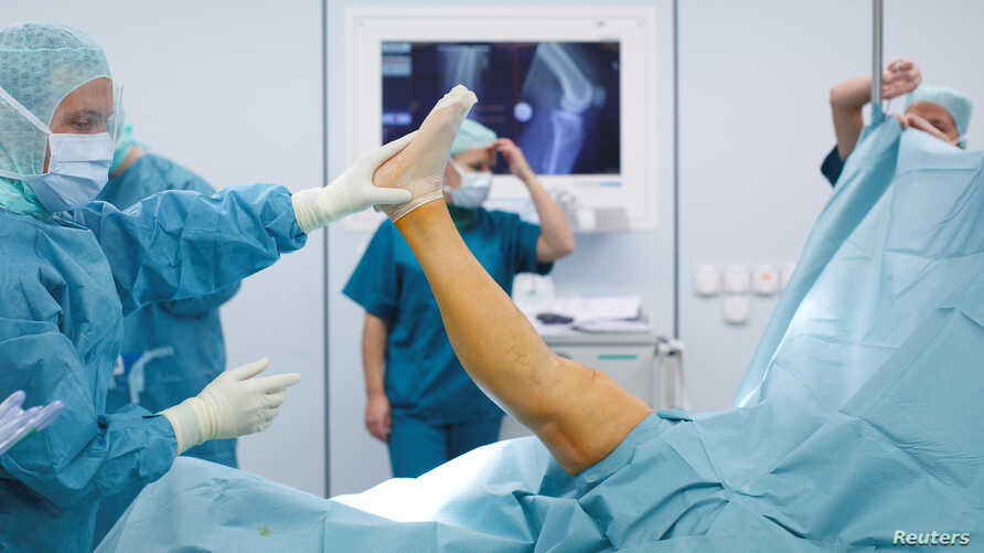 FILE - Doctors and medical staff work during knee prosthesis surgery in an operation room at the hospital of the Canton of Nidwalden in Stans, Switzerland, Oct. 27, 2011.
