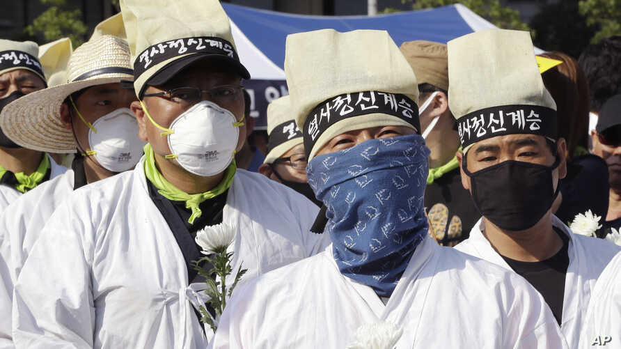 Protesters wear masks as a precaution against the MERS, Middle East Respiratory Syndrome, virus during a rally against government's labor policy in Seoul, South Korea, Sunday, June 7, 2015.