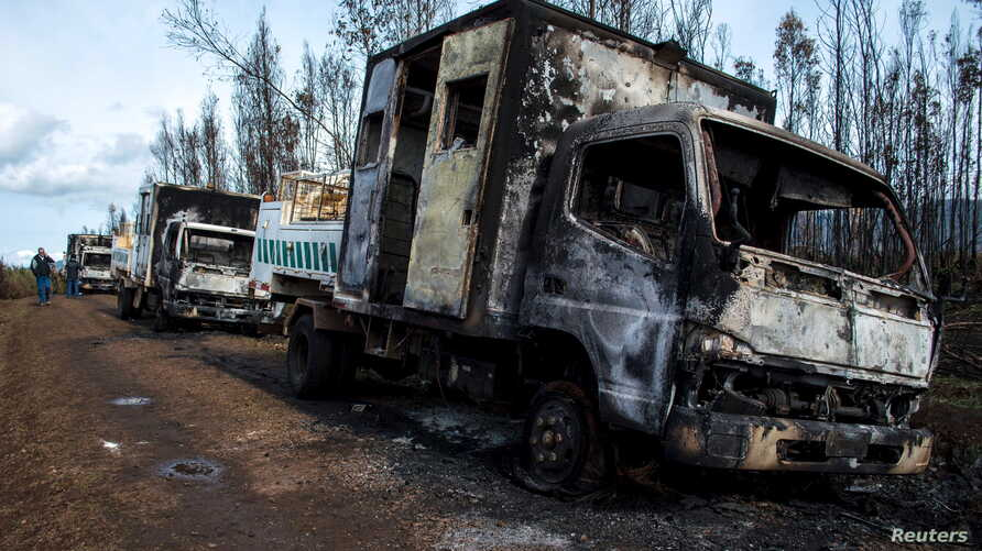 Burnt-out trucks are pictured on a rural road near Angol town, Temuco city, south of Santiago, Chile August 7, 2015. Six trucks and heavy machinery of a forest company were burned in an arson attack in a rural area on the road between Angol and Colli