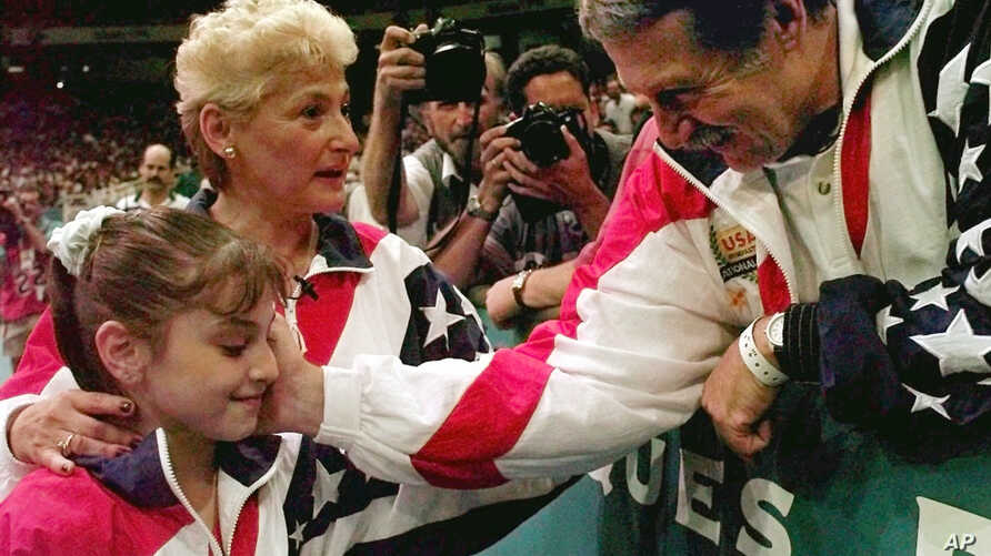 FILE - In this July 23, 1996, photo, Bela Karolyi, right, congratulates Dominique Moceanu, left, after the United States captured the gold medal in the women's team gymnastics competition at the  Summer Olympic Games in Atlanta. U.S. team coach Marth
