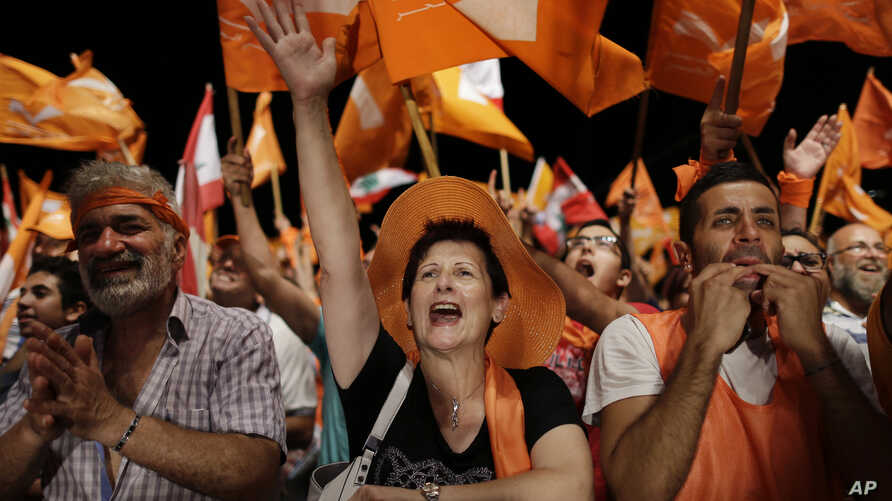 Supporters of Christian leader Michel Aoun hold Free Patriotic Movement and Lebanese flags, during a protest in downtown Beirut, Lebanon, Sept. 4, 2015.