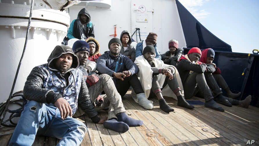 Migrants sit on the deck of the Sea-Eye rescue ship in the Mediterranean Sea, Tuesday, Jan. 8, 2018.