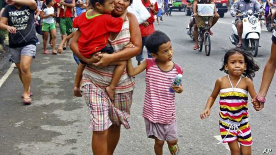Residents rush to higher grounds following tsunami rumors due to a magnitude 6.9 earthquake which hit the island province of Cebu and other central Philippine provinces, February 6, 2012.