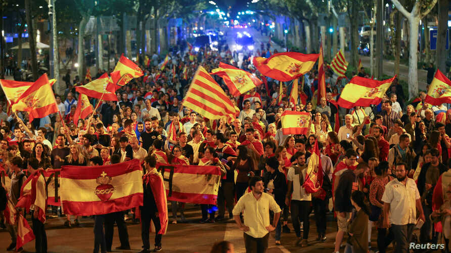 Pro unity demonstrators wave Spanish and Catalan flags during a protest after the Catalan regional parliament declared independence from Spain in Barcelona, Spain, Oct. 27, 2017.
