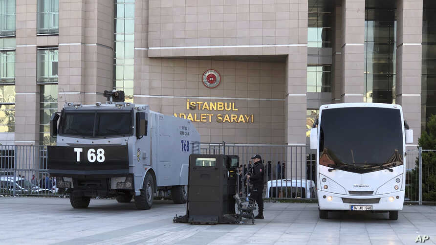 Security cars and an official stand outside the Justice Palace as a trial against Metin Topuz, a Turkish employee of the United States Consulate in Istanbul charged with espionage and attempting to overthrow the Turkish government, began in Istanbul,