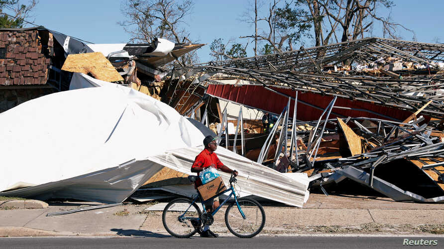 A man carries food and water past a building damaged by Hurricane Michael in Parker, Fla., Oct. 13, 2018.