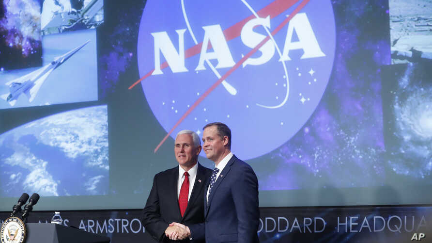 Vice President Mike Pence, left, shakes hands with the new NASA administrator Jim Bridenstine, right, on stage during a swearing-in ceremony, April 23, 2018, at NASA Headquarters in Washington.