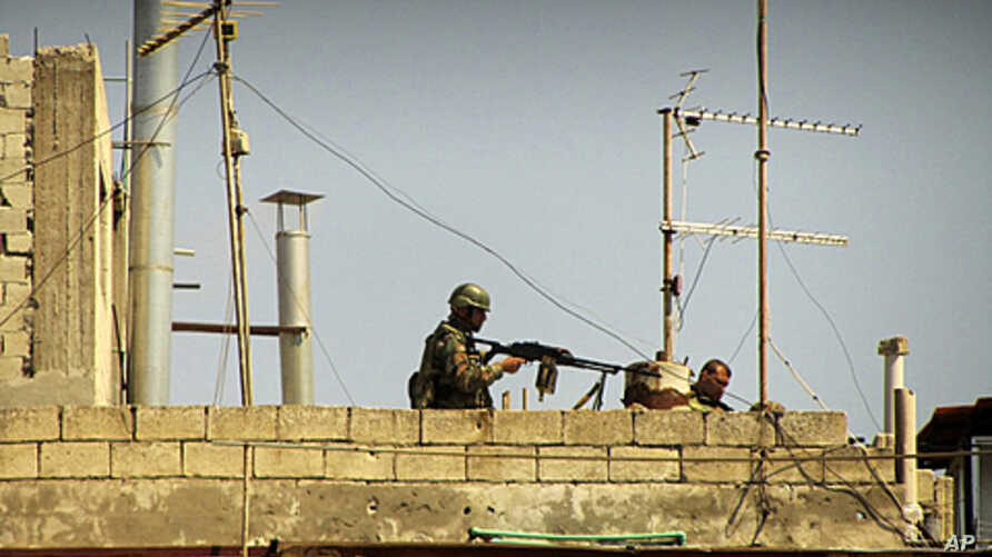 In this undated citizen journalism image made on a mobile phone and acquired by the AP, Syrian soldiers stand on the roof of a building in an undisclosed location in Syria
