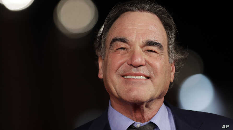 """FILE- Director Oliver Stone poses for photographers as he arrives for the screening of his movie """"Snowden,"""" at the Rome Film Festival, in Rome, Oct. 14, 2016."""
