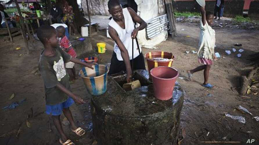 Boys collect water at a well in Liberia's capital Monrovia. (File Photo)