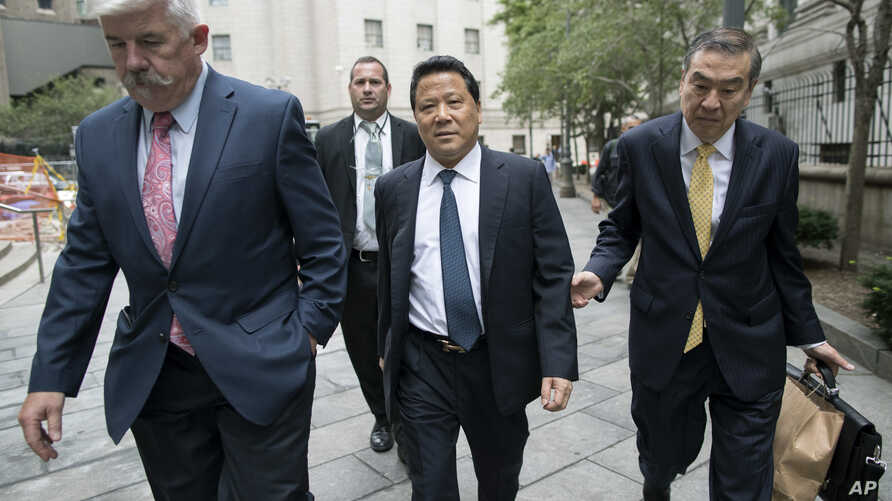 Ng Lap Seng, center, leaves federal court in Manhattan, July 27, 2017.