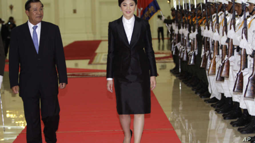 Cambodia's Prime Minister Hun Sen, left, walks together with Thai counterpart Yingluck Shinawatra, center, as she reviews an honor guard inside the Peace Palace in Phnom Penh, Cambodia, Thursday, Sept. 15, 2011