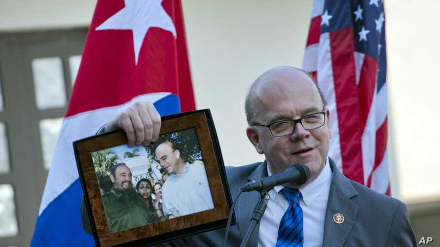 U.S. Democratic congressman for the state of Massachusetts and House Rules Committee Chairman Rep. Jim McGovern holds up a framed archival image that shows him and Fidel Castro, during the inauguration of a conservation center in Havana, Cuba, March