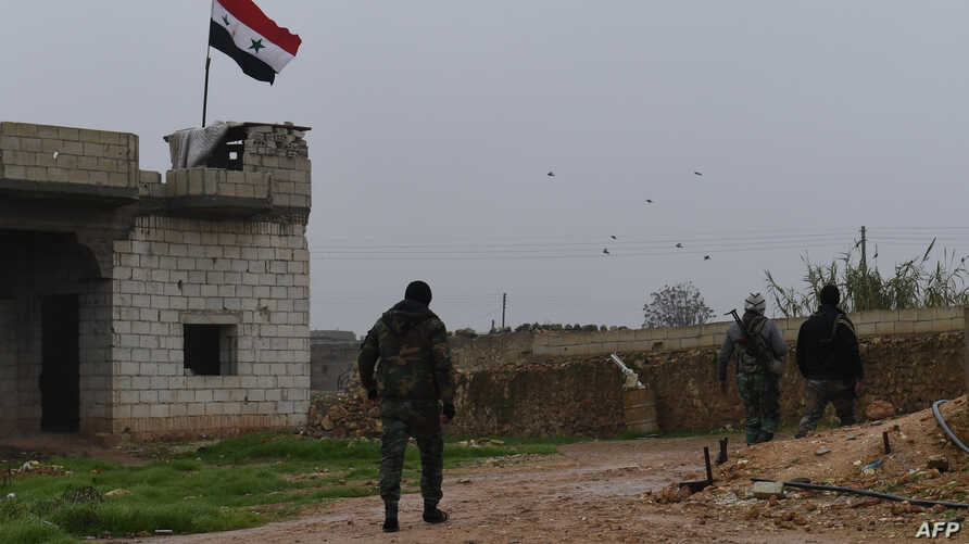 A picture taken on Dec. 30, 2018, shows a Syrian national flag flying over a building as regime forces gather in the southern countryside of the northern Kurdish-controlled city of Manbij.