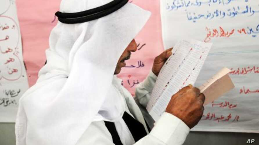 An Egyptian man reads a ballot form preparing to vote at a polling station in El Arish, in the northern part of Egypt's Sinai Peninsula, January 3, 2012.