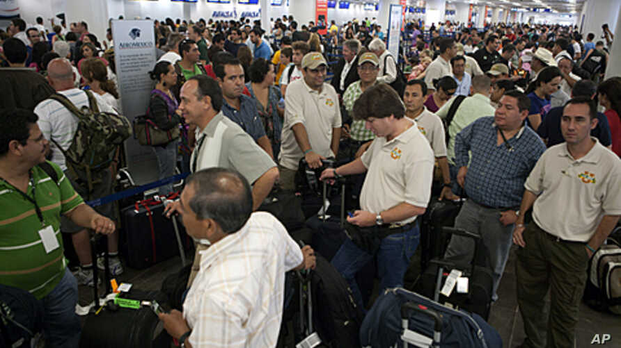 Tourists wait to check their documents at Cancun airport, Mexico, as they prepare to return home, October 26, 2011.