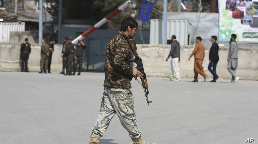 An Afghan security police walks in the site of explosion in Kabul, Afghanistan, March 21, 2019.