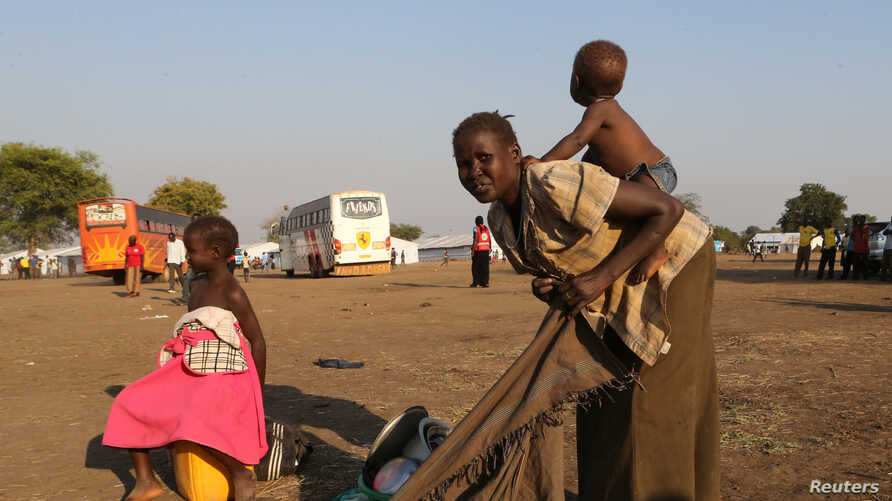 A refugee mother from South Sudan prepares to carry her child on her back on arrival at Bidi Bidi refugee's resettlement camp near the border with South Sudan, in Yumbe district, northern Uganda, Dec. 7, 2016.