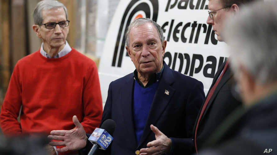Former New York City Mayor Michael Bloomberg, center, speaks during a news conference after touring the Paulson Electric Co., Dec. 4, 2018, in Cedar Rapids, Iowa.