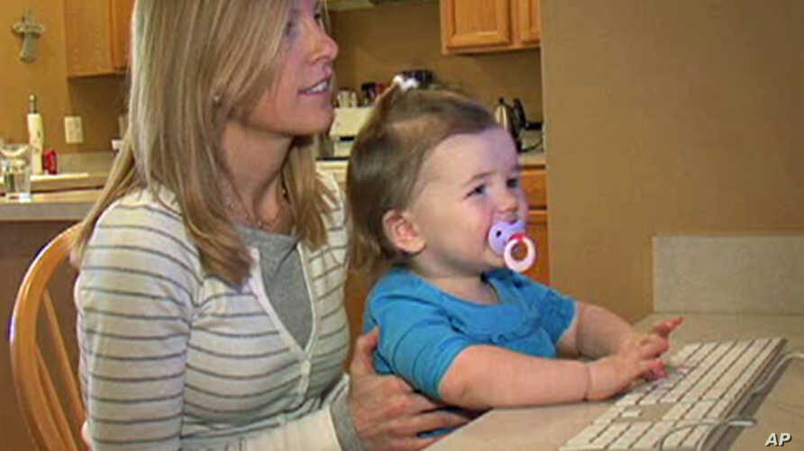 Lilliana Robinson, 2, plays games on Kneebouncers.com while sitting on her mom, Holly's, lap.  Dad, Jim, is one of the creative minds behind the Web Site.