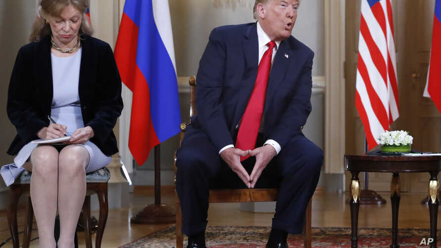 In this July 16, 2018 file photo interpreter Marina Gross, left, takes notes when U.S. President Donald Trump talks to Russian President Vladimir Putin at the beginning of their one-on-one-meeting at the Presidential Palace in Helsinki, Finland.